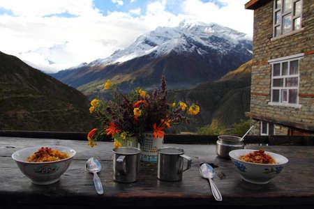Desayuno en la monta�a - el detalle de dos cuencos, flores, vasos, con vistas a las monta�as Foto de archivo - 15735124