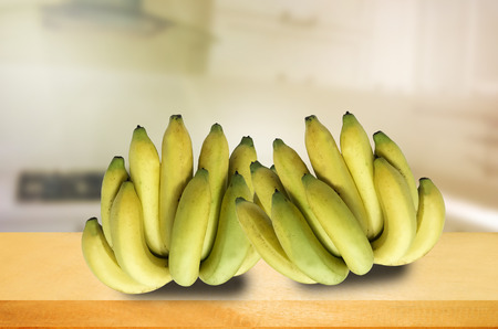 banana on  wooden table and blurred kitchen background.