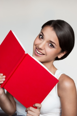 female in casual outfit holding red book