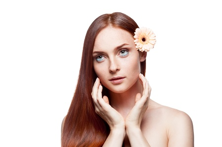 young red-haired female with gerbrera flower in hair photo