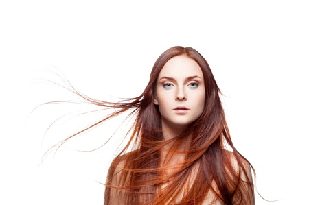 horizontal studio beauty portrait of young attractive green-eyed caucasian female with long natural blowing shiny red hair and perfect clean skin