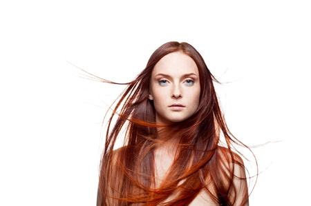 horizontal studio beauty portrait of young attractive green-eyed caucasian female with long natural blowing shiny red hair and perfect clean skin which looking at camera with calm peaceful expression on her face isolated on white background  professional