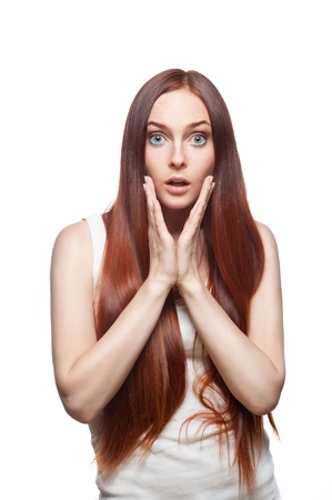 Vertical studio portrait of young attractive green-eyed caucasian female with long natural straight shiny red hair and perfect clean skin dressed in white casual outfit