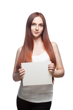 vertical studio portrait of young attractive green-eyed caucasian female with long natural straight red hair which holding white empty cardboard sign