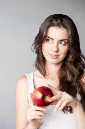 thoughtfull young casual caucasian girl with red apple photo