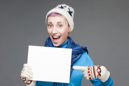 young cheerful girl with sign on gray background photo