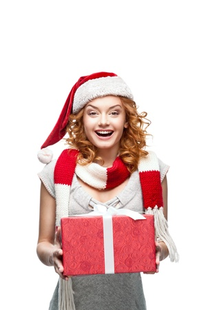 young red-haired happy smiling girl holding christmas gift photo