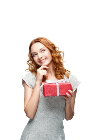 young red-haired casual girl with red gift looking away with thoughtful expression on face  Stock Photo - 15752658