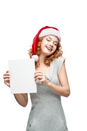 young casual happy smiling caucasian girl in santa hat looking at camera and holding sign  Stock Photo - 15784268