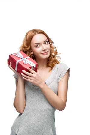 dreamy eyed: young thoughtful happy smiling girl holding gift