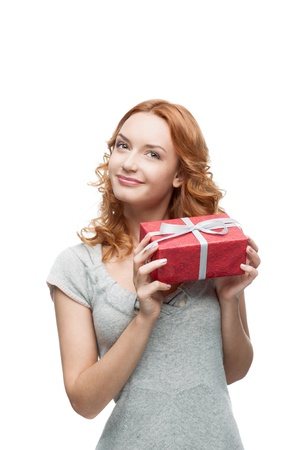 dreamy eyed: young red-haired happy smiling girl holding gift