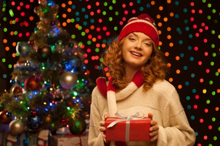 young smiling woman holding red christmas gift Stock Photo