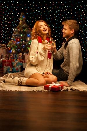felice giovane coppia sorridente casual con bicchieri di vino pi� di albero di Natale e le luci su sfondo profondit� poco profonda di luce calda campo Archivio Fotografico