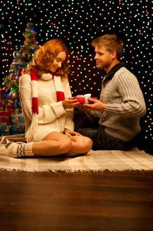 young happy smiling casual couple making a present over christmas tree and lights on background  shallow depth of field  warm light Stock Photo