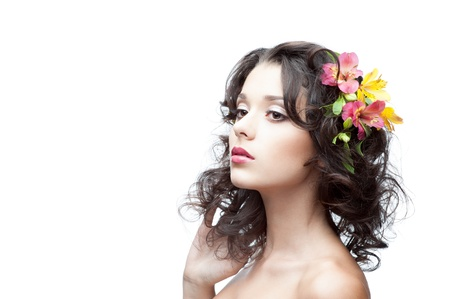 portrait of young attractive caucasian woman with lily flowers in hair Stock Photo