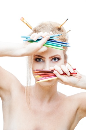 young blond caucasian girl with brushes in hair holding color pencils while looking at camera