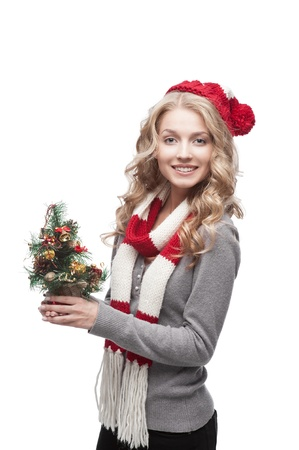 young blond smiling casual woman in red scarf and hat holding christmas tree Stock Photo - 15971547