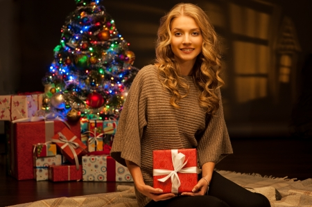 jungen gl�cklich l�chelnde casual woman holding red Geschenk �ber Weihnachtsbaum und Lichter im Hintergrund warmes Licht Lizenzfreie Bilder