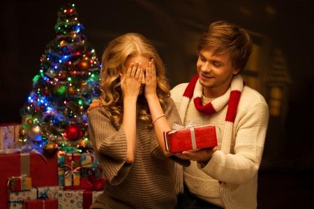 felice giovane coppia sorridente casuale presentazione regalo rosso su albero di Natale e le luci su sfondo chiaro calda