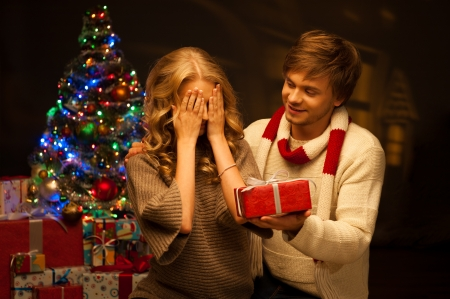 red christmas lights: young happy smiling casual couple presenting red gift over christmas tree and lights on background  warm light