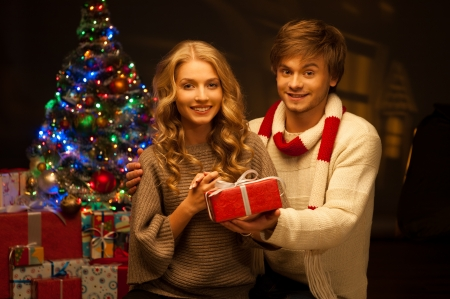 young happy smiling casual couple holding red gift over christmas tree and lights on background  warm light photo