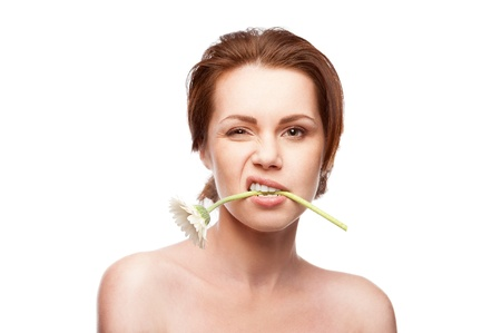 beauty portrait of young caucasian brunette winking woman with flower in mouth isolated on white photo