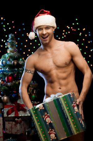 naked man: young naked man in santa hat holding big christmas gift over christmas tree and lights on background