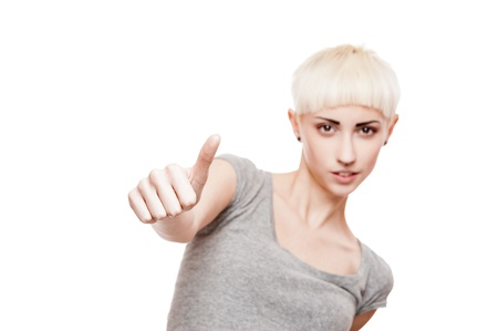 young casual caucasian blond woman in gray t-shirt showing thumbs-up isolated on white photo