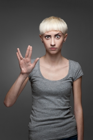 spoke: young casual caucasian blond woman in gray t-shirt showing Spoke sign isolated on gray