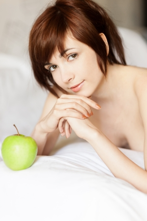 young red-haired caucasian girl lying with green apple and gently smiling while looking at camera photo
