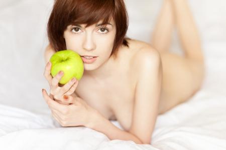giovane ragazza dai capelli rossi caucasica che si trova con mela verde e delicatamente sorridente mentre guardando la fotocamera Archivio Fotografico