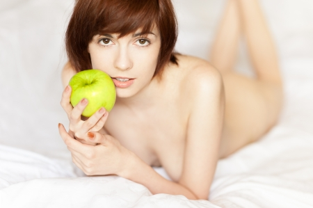 junge rothaarige M�dchen kaukasisch liegend mit gr�nem Apfel und sanft l�chelnd, w�hrend looking at camera Lizenzfreie Bilder