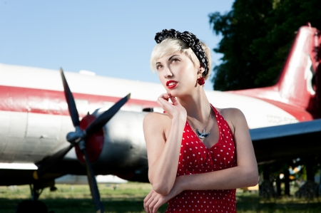 outdoors pin-up portrait of young blond thoughtful caucasian woman in red retro dress  photo