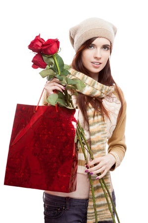 young smiling casual causasian brunette woman holding red roses and shopping bag  isolated on white photo