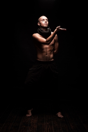young caucasian male dancer showing move over black background photo