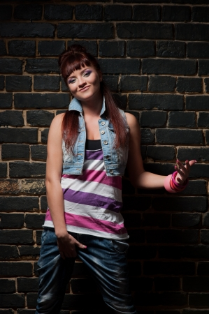 young stylish caucasian smirking girl in hip-hop clothing lean against black brick wall Stock Photo - 16242040