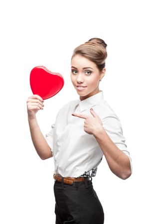 young smiling caucasian brunette business woman holding and pointing at red Valentine heart Stock Photo - 16242079
