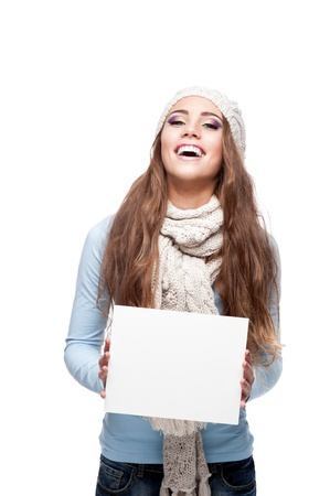young shappy smiling caucasian brunette woman in winter clothing holding sign isolated on white photo