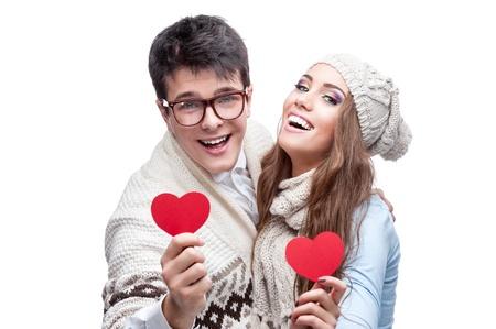 giovane casuale caucasico coppie bruna in abbigliamento invernale in possesso di cuori rossi e guardando la fotocamera con sorriso felice