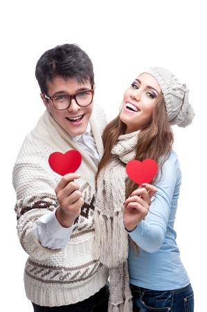 casual giovane coppia indoeuropea bruna in abbigliamento invernale in possesso di cuori rossi e guardando la fotocamera con sorriso felice
