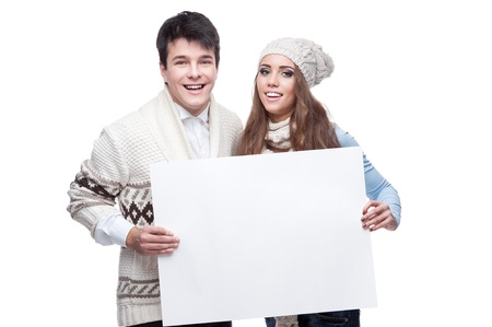 young casual caucasian brunette couple in winter clothing holding big sign and looking at camera with happy smile photo