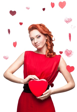 young smiling red-haired caucasian woman in red dress holding red heart isolated on white Stock Photo - 16311957
