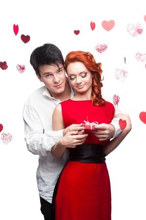 l�chelnden jungen Mann und Frau im roten Kleid h�lt kleinen roten Geschenk-