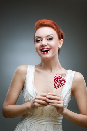 young smiling caucasian red-haired woman in white dress holding lollipop over gray background Stock Photo - 16518909