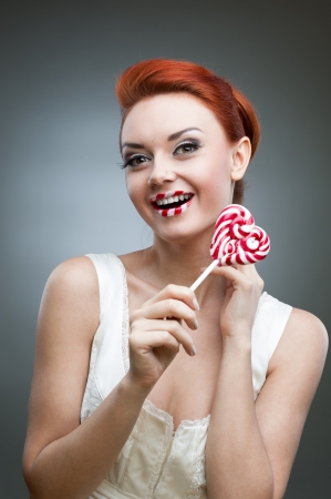 young smiling caucasian red-haired woman in white dress holding lollipop over gray background Stock Photo - 16519620