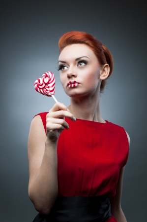 young sexy caucasian red-haired woman in red dress holding lollipop over gray background