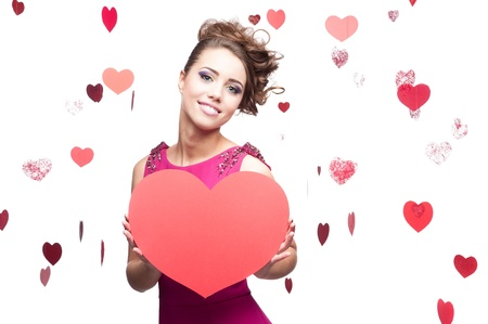young cheerful caucasian brunette woman holding big red paper heart