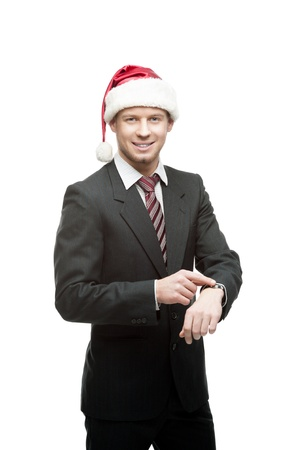 young smiling caucasian businessman in black suit and santa hat pointing at watch isoalted on white