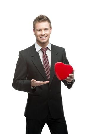 giovane, allegro, sorridente uomo d'affari caucasico in vestito nero che tiene cuore rosso isoalted su bianco Archivio Fotografico