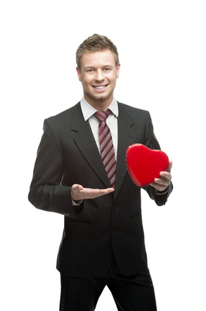 male costume: young cheerful smiling caucasian businessman in black suit holding red heart isoalted on white